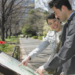 Asian couple looking at  map in urban park