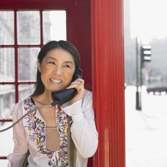 Asian woman using public telephone box in urban area in London