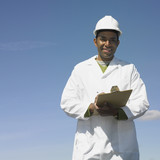 Man with hard hat and clipboard smiling outdoors