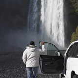 Man in winter jacket leaning on truck and looking at waterfall