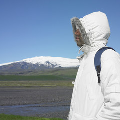 Man wearing winter jacket and backpack with snow-capped mountain in background