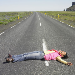 Young woman laying in middle of road laughing