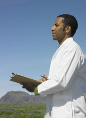 Man wearing lab coat and holding clipboard outdoors