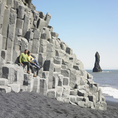 Couple sitting on rock ledge at beach