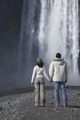 Couple in winter clothes looking at waterfall