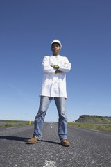 Man wearing hard hat and lab coat standing in middle of deserted road