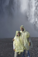 Couple wearing rain ponchos in front of waterfall