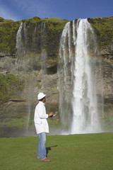 Man with hard hat and clipboard looking at waterfall