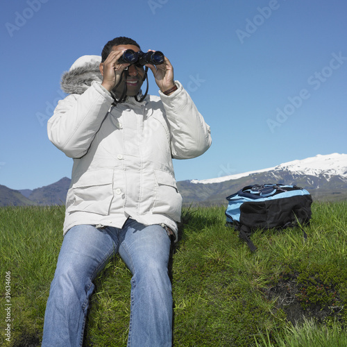 African man sitting in grass wearing winter jacket with binoculars and backpack