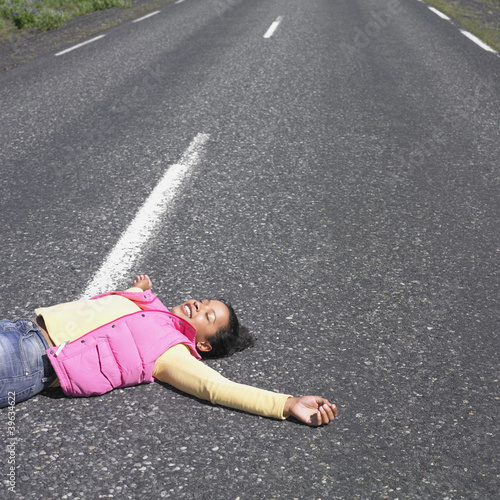 Young woman laying in middle of road smiling