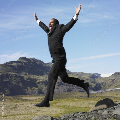 Businessman jumping off rocks in deserted rural area