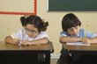 Children writing at desks in classroom