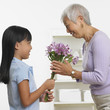 Asian girl giving grandmother bouquet of flowers