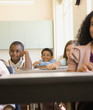 Young students smiling at desks in classroom