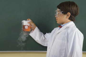 Boy wearing lab coat and goggles and holding steaming beaker in classroom
