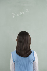Hispanic girl looking at formula written on blackboard