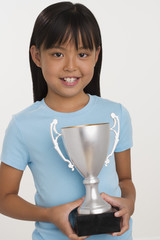 Young Asian girl holding trophy and smiling