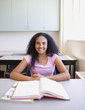 African girl smiling at desk in classroom