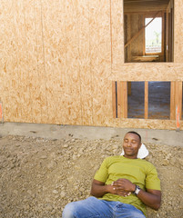 Male construction worker sleeping at construction site