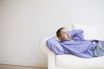 African man sleeping on sofa