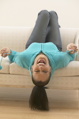 Woman upside down on sofa laughing