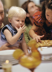 Young girl and toddler sticking fingers in pie