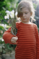 Young girl with butterfly on arm outdoors