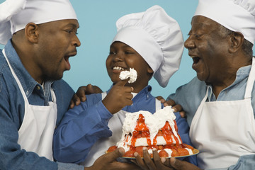 Multi-generational African male family members in chef's hats with cake