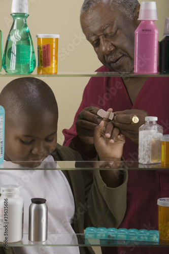 African grandfather bandaging grandson's finger in front of medicine cabinet