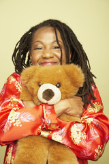 Middle-aged African woman hugging teddy bear