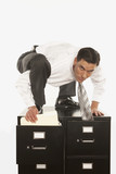 Businessman filing on top of filing cabinet