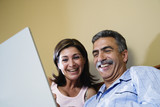 Middle-aged couple smiling at laptop
