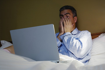 Middle-aged Hispanic man using laptop in bed