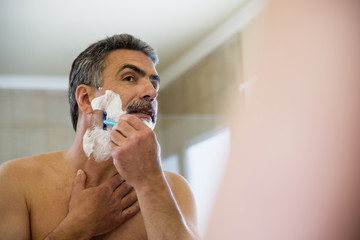 Middle-aged Hispanic man shaving face