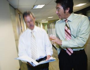 Two businessmen talking in hallway