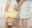 Father holding young son upside down