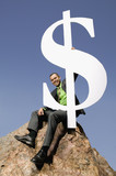 Asian businessman on boulder holding dollar sign