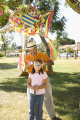 Hispanic girl being blindfolded next to pinata outdoors