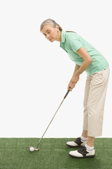 Senior Hispanic woman putting on golf green