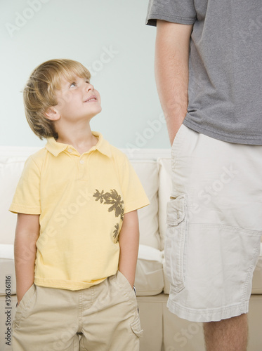 Young boy smiling up at father