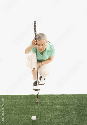 Senior Hispanic woman lining up golf shot