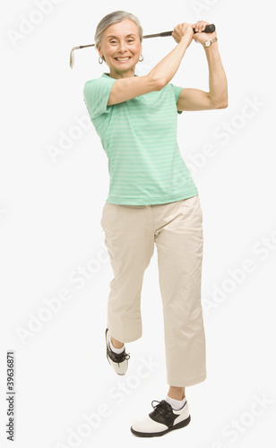 Senior Hispanic woman swinging golf club