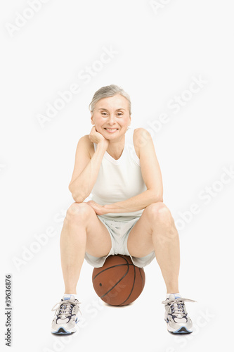 Senior Hispanic woman sitting on basketball