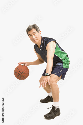 Senior Asian man playing basketball