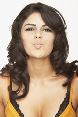 Portrait of Hispanic woman blowing kiss