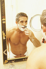 Middle-aged man shaving in mirror