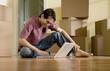 Hispanic man typing on laptop in new house