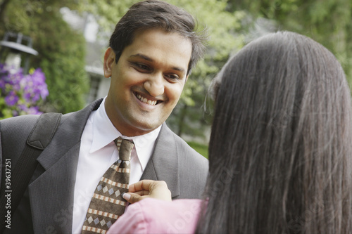 Indian woman adjusting husband's necktie