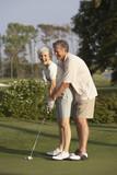 Senior man helping wife with golf swing