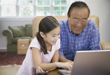 Asian grandfather and granddaughter looking at laptop